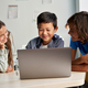 Three diverse schoolmates watching video together on laptop in classroom. - PhotoDune Item for Sale