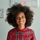 Portrait of cute smiling afro American schoolgirl standing in classroom. - PhotoDune Item for Sale