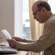 Senior man sitting at table at home alone with paperwork - PhotoDune Item for Sale