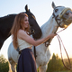 Young caucasian beautiful woman taking care of her horse walking at field. - PhotoDune Item for Sale
