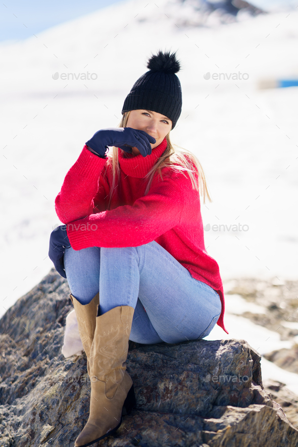 Young woman sitting on a rock in the snowy mountains in winter, in Sierra Nevada, Granada, Spain. - Stock Photo - Images