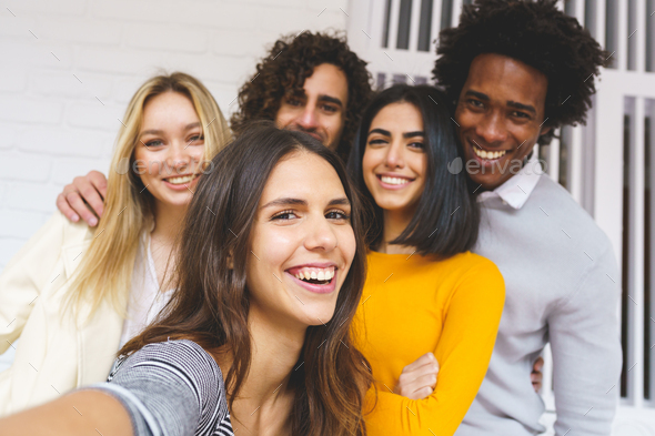 Multi-ethnic group of friends taking a selfie together while having fun outdoors. - Stock Photo - Images
