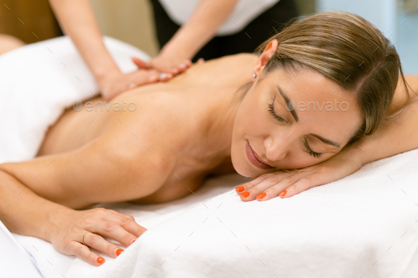 Middle-aged woman having a back massage in a beauty salon. - Stock Photo - Images