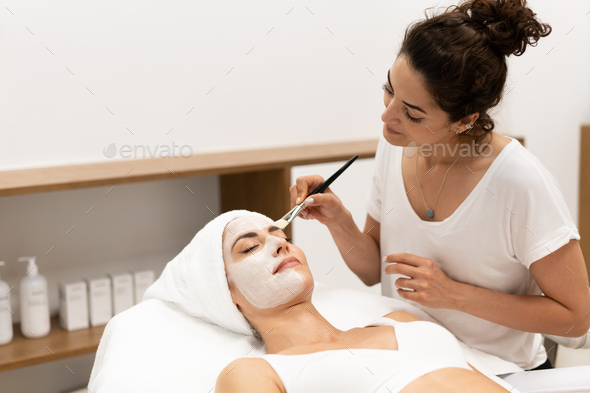 Aesthetics applying a mask to the face of a Middle-aged woman in modern wellness center. - Stock Photo - Images