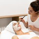 Aesthetics applying a mask to the face of a Middle-aged woman in modern wellness center. - PhotoDune Item for Sale