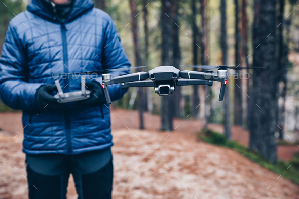Man navigating a flying drone in the forest. - Stock Photo - Images