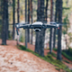 Modern Drone with camera flying in the forest. - PhotoDune Item for Sale