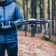 Man navigating a flying drone in the forest. - PhotoDune Item for Sale