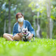 A woman wearing a medical mask sits on the lawn with a white French bulldog. - PhotoDune Item for Sale