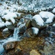 Small stream among wet stones and white snow in the picturesque Carpathian mountains in Ukraine - PhotoDune Item for Sale
