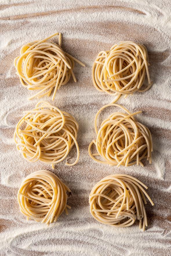 Italian pasta nest. Uncooked spaghetti nest and flour. - Stock Photo - Images