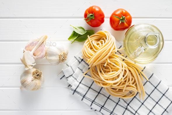 Italian pasta nest, basil, garlic and tomato. Uncooked spaghetti nest - Stock Photo - Images