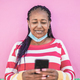Senior african woman using mobile phone in the city while wearing safety face mask under chin - PhotoDune Item for Sale
