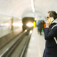 man passenger with backpack talking on cellphone, waiting for the train at subway station platform - PhotoDune Item for Sale
