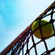 Yellow tennis ball hits in the net during game. Blue sky at background - PhotoDune Item for Sale
