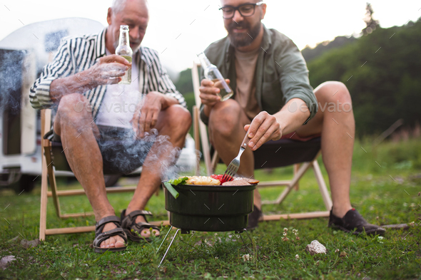 Mature man with senior father talking at campsite outdoors, barbecue on caravan holiday trip - Stock Photo - Images