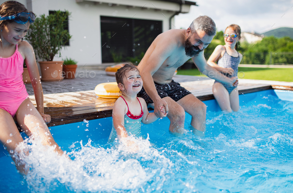 Father with three daughters outdoors in the backyard, playing in wimming pool - Stock Photo - Images