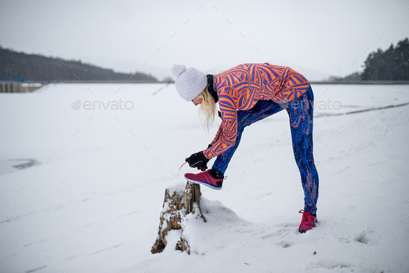 Active senior woman outdoors in snowy winter, tying shoelaces - Stock Photo - Images