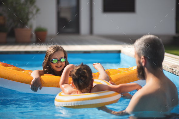 Father with three daughters outdoors in the backyard, playing in swimming pool - Stock Photo - Images