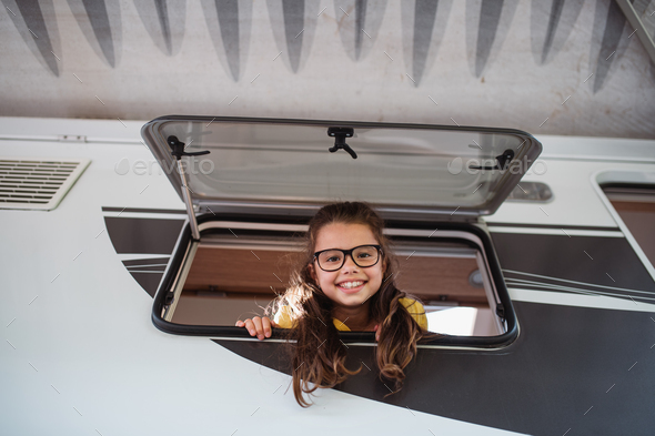 Happy small girl looking out through caravan window and looking at camera, family holiday trip - Stock Photo - Images