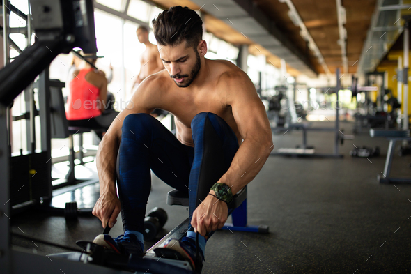 Young fit man exercising in a gym to stay healthy. Sport people workout concept - Stock Photo - Images