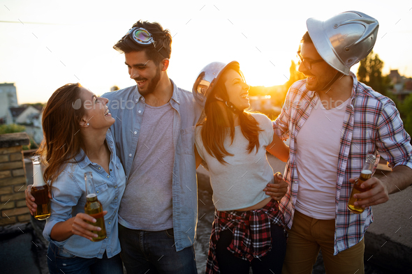 Happy group of friends with drinks having fun at rooftop party - Stock Photo - Images