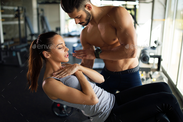 Personal trainer assisting woman to lose weight. Sport exercise people healthy lifestyle concept - Stock Photo - Images