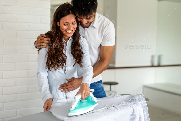 Happy young couple doing the ironing together at home - Stock Photo - Images