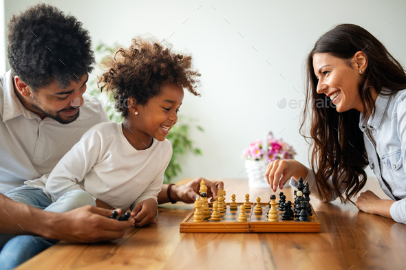 Parents and child playing chess while spending time together at home. Family love education concept - Stock Photo - Images