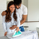Happy young couple doing the ironing together at home - PhotoDune Item for Sale