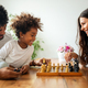 Parents and child playing chess while spending time together at home. Family love education concept - PhotoDune Item for Sale