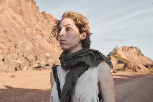 Female refugee walking among mountains - Stock Photo - Images