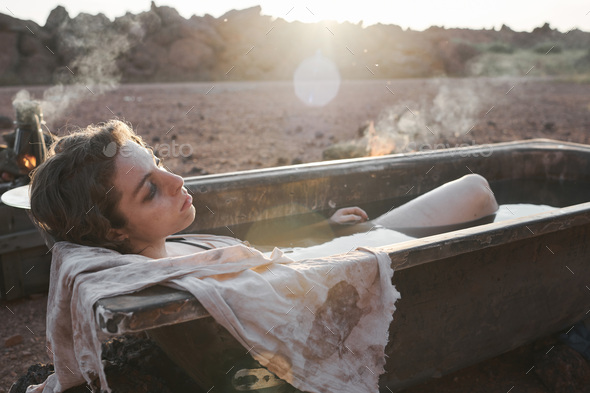 Woman lying in the bath in the desert - Stock Photo - Images