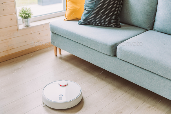 Wireless Robotic vacuum cleaner  cleaning a wooden floor in living room - Stock Photo - Images