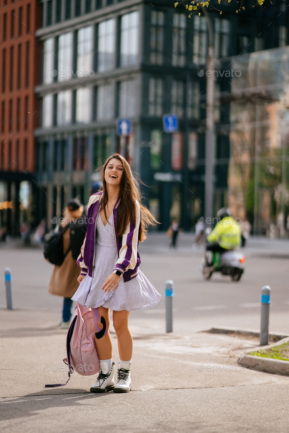 Young beautiful woman with backpack posing at camera - Stock Photo - Images