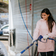 Brunette from a high-pressure hose applies a cleaner on the car - PhotoDune Item for Sale