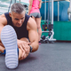 Sportsman stretching leg sitting in the gym - PhotoDune Item for Sale