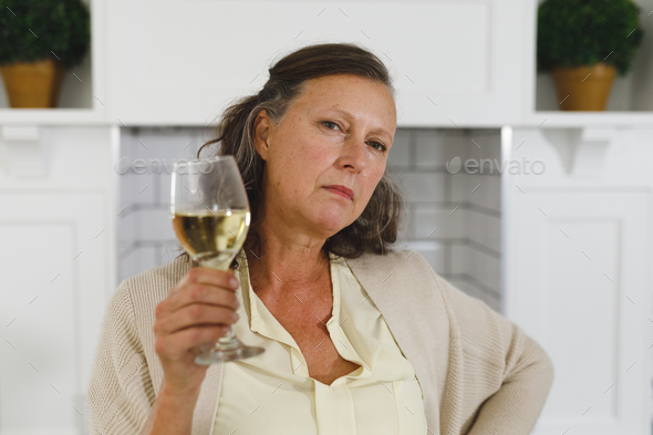 Portrait of senior caucasian woman in modern kitchen, holding glass of wine, looking to camera - Stock Photo - Images