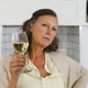 Portrait of senior caucasian woman in modern kitchen, holding glass of wine, looking to camera - PhotoDune Item for Sale