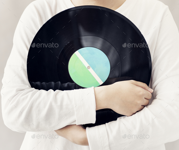 Closeup of woman holding music vinyl record disc - Stock Photo - Images