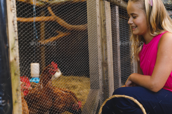 Smiling caucasian girl collecting eggs from hen house in garden - Stock Photo - Images