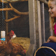 Smiling caucasian girl collecting eggs from hen house in garden - PhotoDune Item for Sale