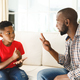 Happy african american father with son sitting on couch in living room talking sign language - PhotoDune Item for Sale