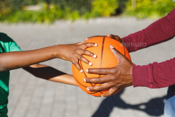 Midsection of african american father and son holding basketball together in garden - Stock Photo - Images