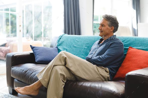 Happy senior caucasian man in living room sitting on sofa - Stock Photo - Images