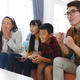 Smiling asian parents with son and daughter sitting on couch watching tv with popcorn - PhotoDune Item for Sale