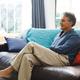 Happy senior caucasian man in living room sitting on sofa - PhotoDune Item for Sale