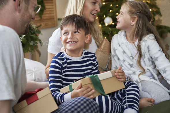 Family sharing the Christmas presents in bed - Stock Photo - Images