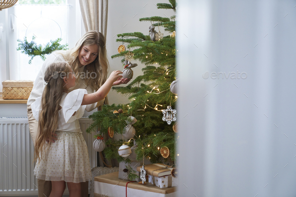 Little girl decorating the Christmas tree with mum - Stock Photo - Images