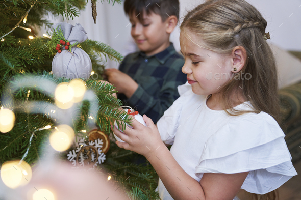 Sibling decorating Christmas tree together - Stock Photo - Images
